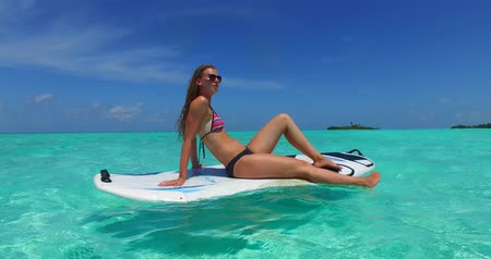 Мальдивы : v11972 one 1 beautiful young girl in bikini sunbathing on surfboard paddleboard and relaxing by the aqua blue sea water on white sand in the sun