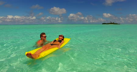 banhos de sol : two people inflatable sunbed romantic young people couple with drone aerial flying view on a tropical island of white sand beach and blue sky and sea