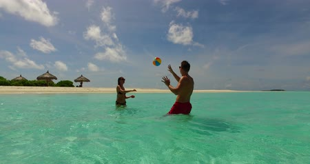eye ball : 2 people playing ball romantic young couple on a tropical island of white sand beach and blue sky and sea
