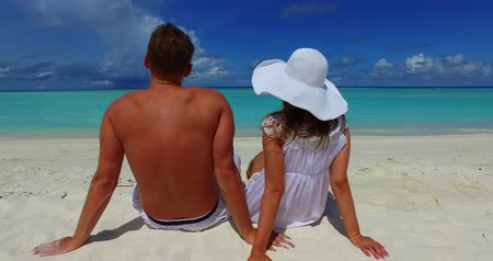 dron : 2 people sitting together a romantic young couple on a tropical island of white sand beach and blue sky and sea Wideo