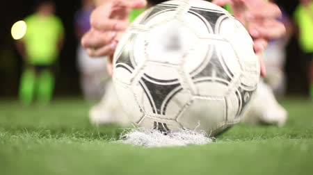 Soccer ball placed on penalty spot of green field by football player. Close up