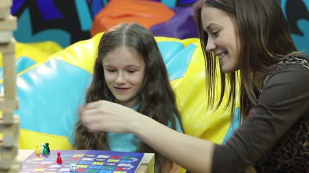 кусок : Smiling girl plays board game with sister, family bonding, education