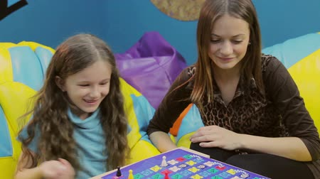 o : Girl teaches happy little sister, playing board game, having fun