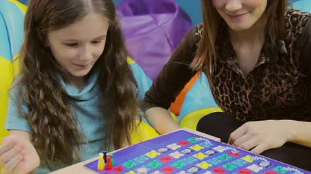 bordo : Woman playing board game smiling girl, mother teaching child Stock Footage