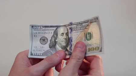 richness : Person holding in hands and turning over one hundred-dollar bill