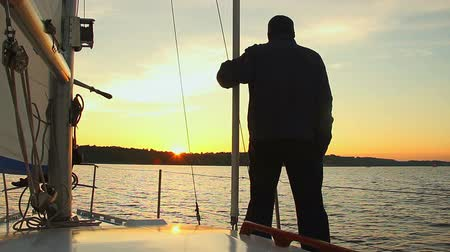 żaglowiec : Silhouette of man standing on sailing yacht and watching sunset Wideo