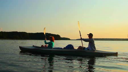evezés : Sportive man and woman paddling boat synchronously, active rest