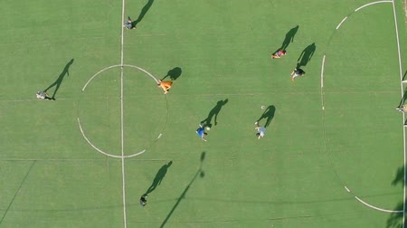 match : Young people playing football (soccer) having rest. Aerial shot