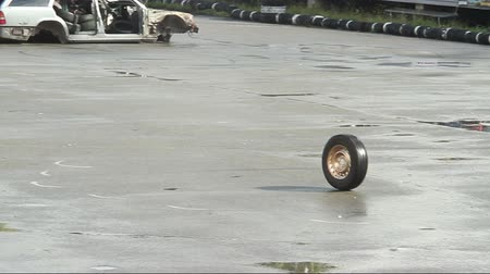 abandonment : Car wheel rolling on asphalt after accident, crash. Junkyard