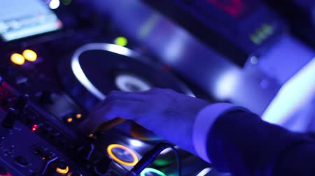 tweak : Male DJ hands pressing buttons on control deck, platter turning