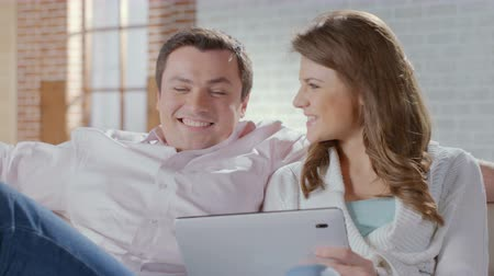 ebay : Happy couple sitting on couch with tablet pc. Online shopping Stock Footage