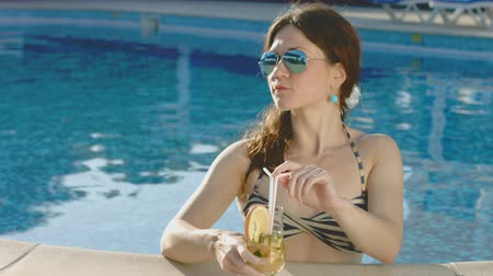 бикини : Attractive woman relaxing in pool, drinking cocktail on vacation