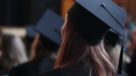 čepice : Young woman in academic dress and cap clapping, hopes for successful future