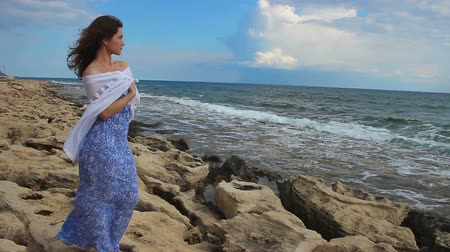 gentleness : Sad lonely young woman looking at stormy sea, waves splashing, rocky shore, wind Stock Footage
