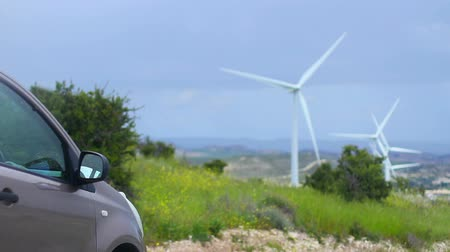 tesla car : Electric car, wind turbines rotating, green energy source, clean environment