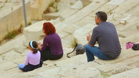 dionysus : Parents and daughter sitting on ancient amphitheater seats, family travel Stock Footage