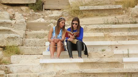dionysus : Two beautiful women reading tourist guide, planning sightseeing tour together