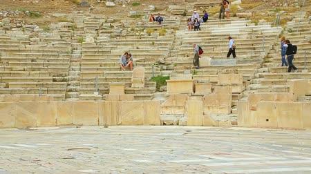 amphitheatre : Pan shot of amphitheatre seats at Dionysus Theatre, people having rest, walking