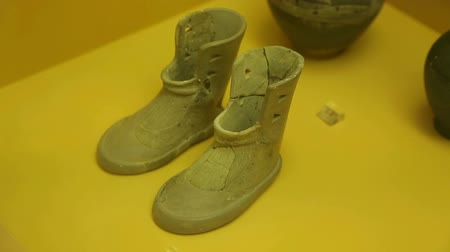 terracota : Pair of miniature terracotta boots, ancient Greek offering from cremation burial Stock Footage