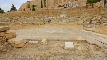 dionysus : Amphitheater of seats rising from stage at Theater of Dionysus remains in Athens Stock Footage