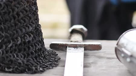 knightly : Close-up shot of sharp steel sword and chain mail armour lying on wooden table