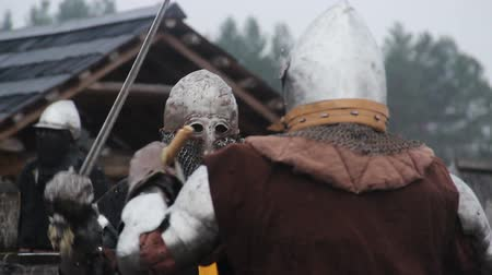 reencenação : Brave warriors in medieval knight armour suits fighting with swords in the rain