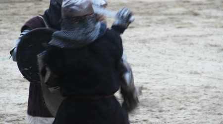 reencenação : Sword fight between two men wearing historic armor suits and steel helmets Stock Footage