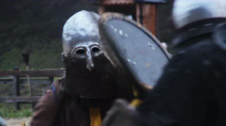 reencenação : Man in steel helmet with chain mail mask attacking rival in violent sword fight Stock Footage