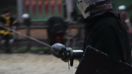 reencenação : Men with sharp steel swords and shields starting to fight on tournament field