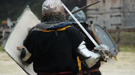reencenação : Two courageous knights attacking each other with swords, defending with shields