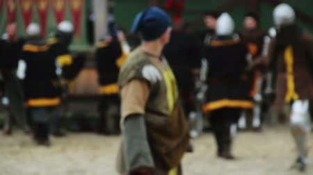 munitions : Defocused people in medieval suits preparing for historic fight reenactment