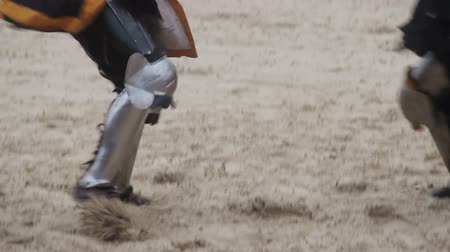 reencenação : Two strong knights wearing steel armor fighting actively, medieval tournament