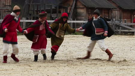 four legs : Medieval performance. Cheerful actors are dancing and jumping on the square