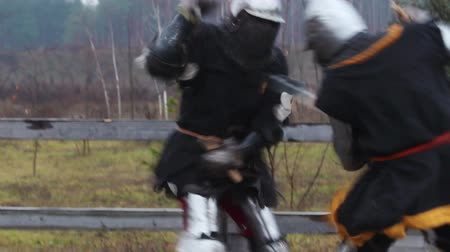 şövalye : Two strong knights in steel armor hitting each other with swords, slow motion