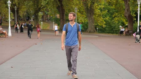 атлетика : Young man with backpack walking around the park, checking out city landmarks