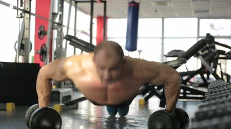 feszült : Professional male athlete doing push-ups in gym, sportsman looking into camera