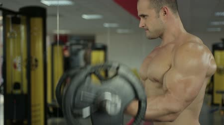 self motivated : Strong muscular man exercising with barbell, looking in mirror during workout Stock Footage