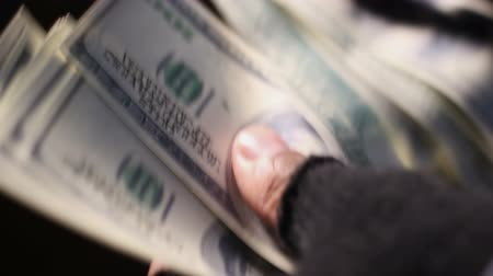 forgery : Closeup shot of male hands in shabby fingerless gloves counting cash in dollars