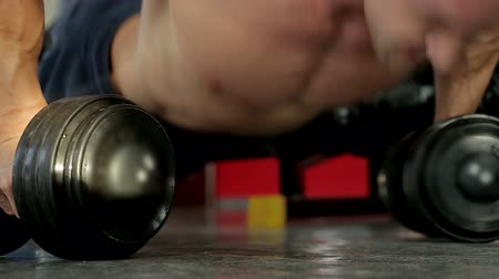 feszült : Strong sportive man doing dumbbell push-up exercise, preparing for competition Stock mozgókép