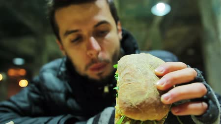 голодный : Hungry poor homeless man eating sandwich with vegetables at charity event