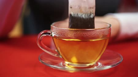 teabag : Teatime, female making black tea, putting teabag in a cup. Person feeling cold
