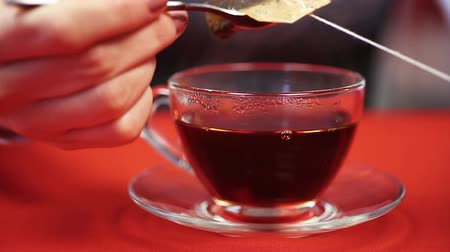 teabag : Process of preparing black tea. Woman pressing teabag with the help of spoon