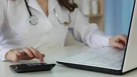 charges : Woman doctor filling in health insurance form on laptop, calculating expenses