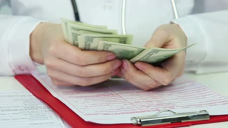 corruptible : Female doctor counting dollars, doctor accepting bribes. Corruption in medicine