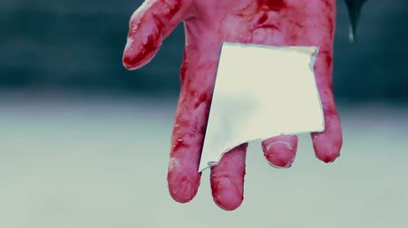 bloodshed : Bloody hand of suicider holding mirror chip, desperate person commits suicide Stock Footage
