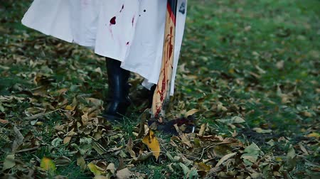 bloodshed : Serial maniac in white coat dragging bloody murder weapon from crime scene