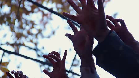 zdjęcia seryjne : Bloodthirsty creatures stretching hands to catch victim, zombie attack in city