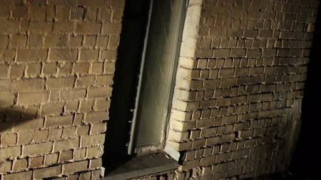 frightful : Scary place, grated window in old brick wall, abandoned building, criminal lair Stock Footage
