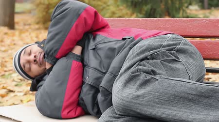 csavargó : Vagabond in jacket and jeans sleeping on bench, trying to keep warm, poverty Stock mozgókép
