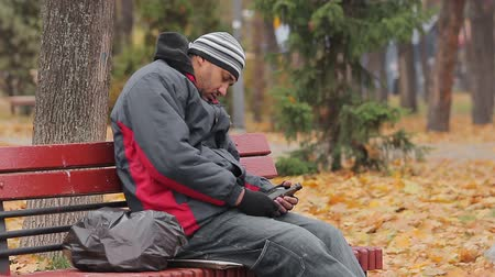 shameful : Male alcohol addict having a nap on bench in autumn park with bottle in hand Stock Footage